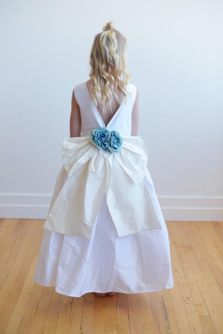 Te back of a flower gir dress with a v back and floor length. The dress has an oversized bow with blue large flowers