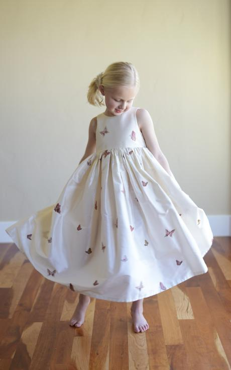 A young junior bridesmaid and a flower girl wearing a beautiful white silk flower girl dress with butterflies embroidered on to it