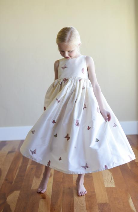 A young flower girl at a wedding twirling in an ivory, pure silk, ankle length flower girl dress with embroidered butterflys.