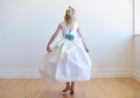 The back of a white silk flower girl dress with an oversized blue bow and blue flowers