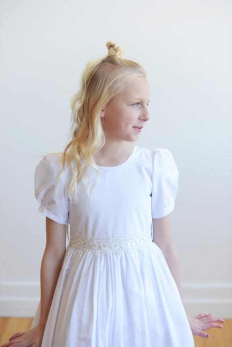 A bespoke first communion dress with puff sleeves and lace belt with lace trim at the hem. The dress  has a full button back.