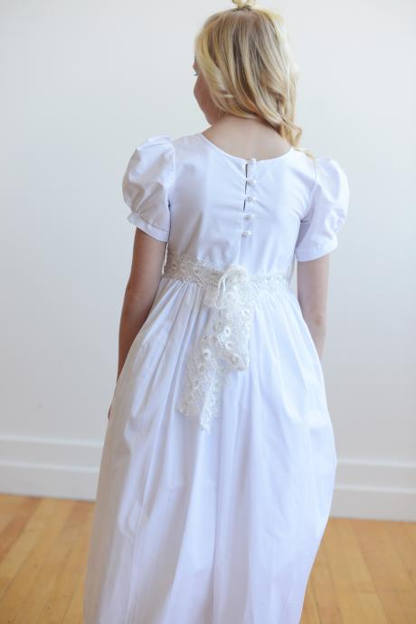 A gril wearing a lace first communion dress with sleeves and a full button back.