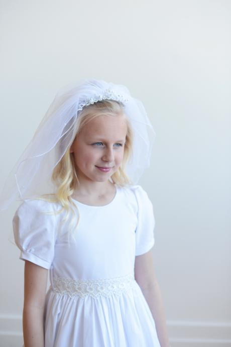 A girl taking her first holy communion wearing a veil with pearls sewn onto the tulle and attached  to a beaded, diamante headband.