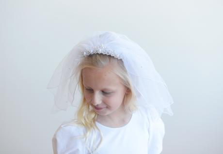 A girl wearing a first communion veil in white with a beaded headband and a double layer of tulle. The tulle has a range of pretty pearls scattered on it.