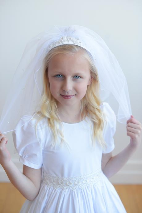 A lace first communion dress with puff sleeves and lace trim at the waist and hem. The dress has a full button back and is worn with a first communion veil.