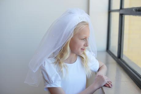 A side view of a first communion veil with a double layer of tulle and a beaded headband. The beading is made of pearls and diamante and are attached to a wide satin headband.