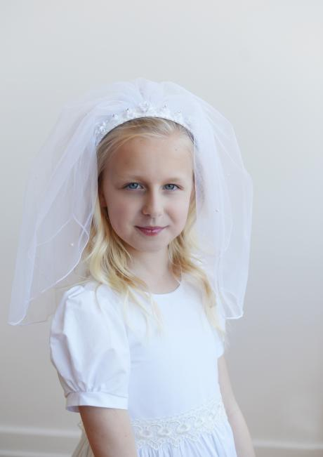 A girl wearing a first communion veil in white. The hair piece has a double veil with a satin beaded headband with flowers sewn onto it.