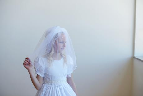 A girl wearing a first communion veil with flowers sewn onto the headband and pretty beaded stitching with pearls sewn into the veil.