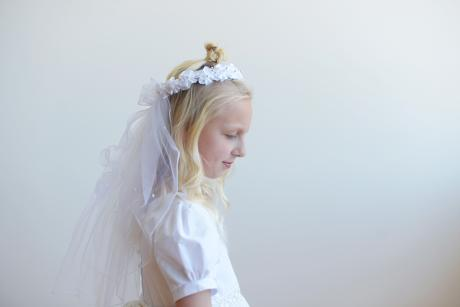A girl wearing a white first communion veil with a beaded crown and a tulle train. The tulle on the train has beading and a ribbon flows down the back.