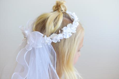 A white first communion crown with pearl beading and a veil. The back of the veil has a large ribbon and there is diamante and pearls scattered on the tulle of the veil.