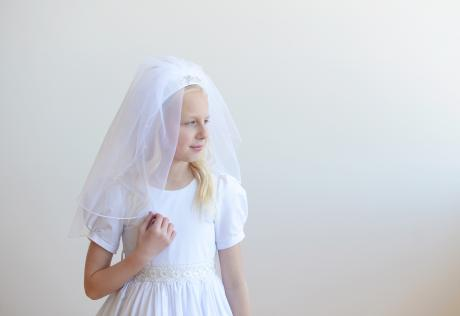 A side view of a first communion veil in white with a decorated satin headband. The headband has pearls, diamante and beading and the veil has pretty, tiny pearls scattered on the tulle.