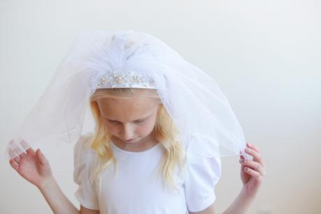 A girl taking her first communion wearing a beaded tulle veil with pearls decorating the veil and pretty beading on the satin headband.