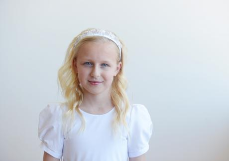 A girl at her first communion wearing a beaded satin first communion headband in white.