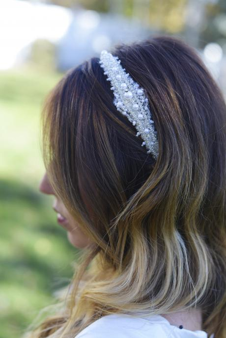 A bridesmaid wearing a pretty pearl and diamante bridal hair accessory on an ivory satin alice band