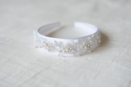 A close up of a first communion headband. The headband is white and made of satin with a hand sewn bead trim.
