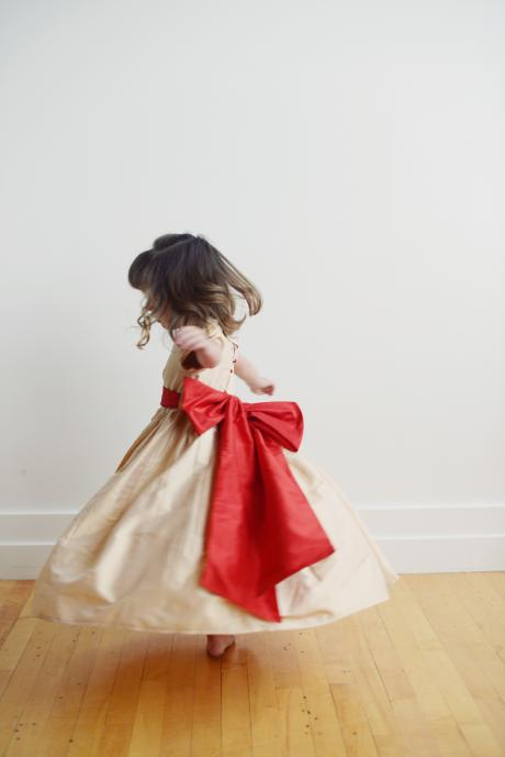 A back view of a toddlers wearing a flower girl dress in gold silk. The dress has a matching big red bow and sash and the dress has covered red silk buttons.