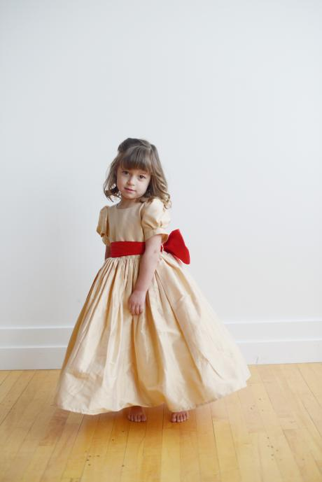 The front of a toddler flower girl dress in gold silk with a red silk bow and matching buttons. The dress has a full petticoat