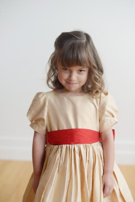 A toddler wearing a gold and red flower girl dress with a big bow and puff sleeves.
