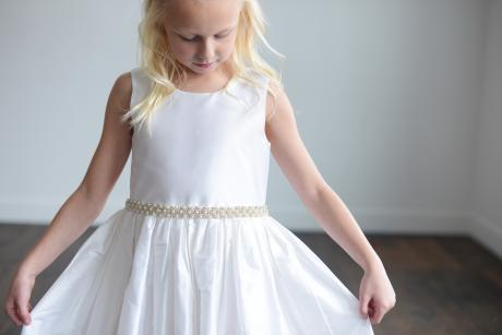 A girl in a church taking her first holy communion wearing a pure white first holy communion dress with pearls at the waist and a full silk skirt.