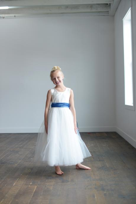 A young flower girl with a toddler and a baby wearing white silk flower girl dresses with royal blue and navy sashes.