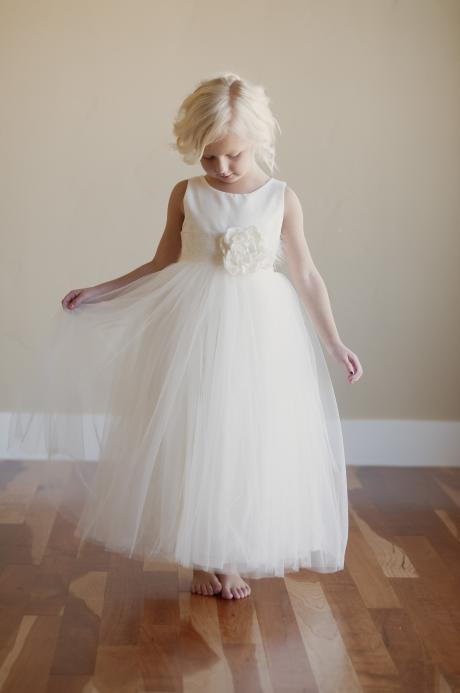 A five year ld girl wearing a cotton or silk flower girl dress with big flower on wide lace sash in ivory