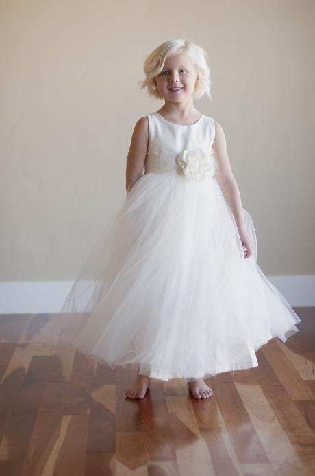 A four year old girl wearing a flower girl dress with lace elasticated belt sash in silk and tulle in ivory or white