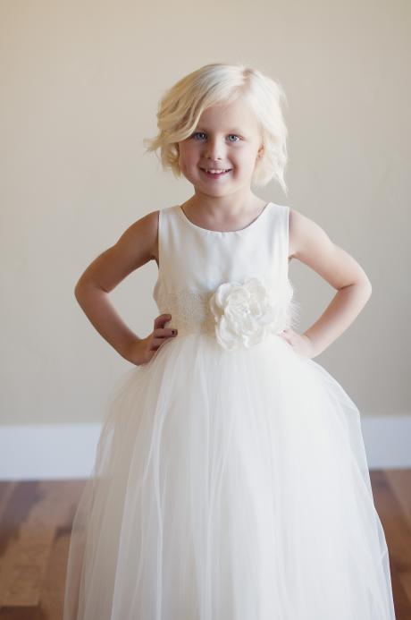 A four year old girl wearing a flower girl dress for junior bridesmaids in ivory or white with elasticated belt and flower enbellishment