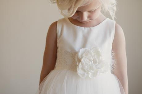 A young girl wearing a silk flower girl dress with lace sash and large flower for junior bridesmaids and flower girls
