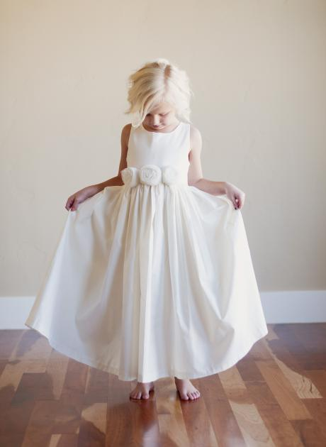 A girl at a wedding holding the ides of her ivory flower girl dress out. The dress is made in cotton and has a very full skirt