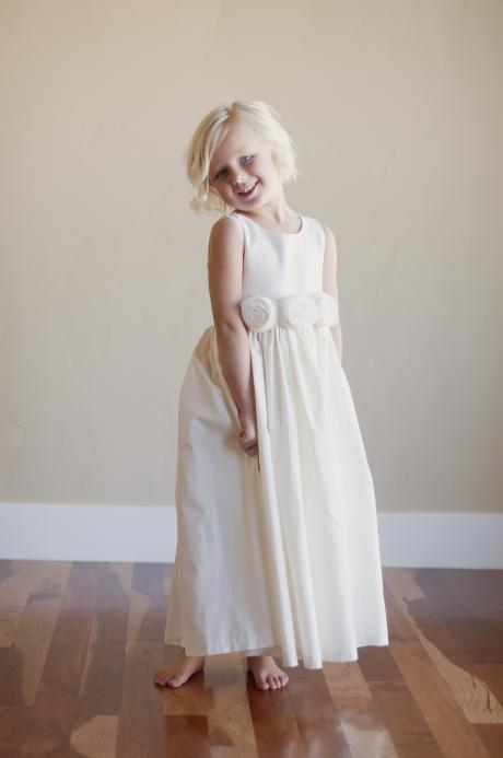 A flower girl standing at a wedding and wearing an ivory, ankle length flower girl dress with roses on th front.