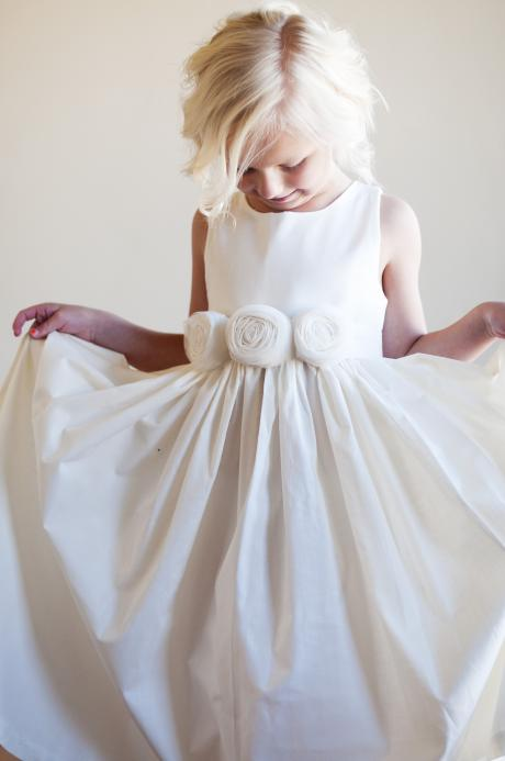 A flower girl at a wedding with a bride wearing matching ivory and white dresses with handmade bespoke rosettes on the  sash.