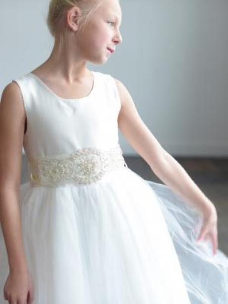 A young flower girl at a wedding wearing a tulle dress with a silk bodice and a diamanté sash