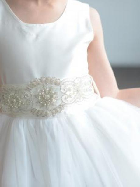 A close up of a girl in a white flower girl dress with a big tulle skirt and diamanté belt.