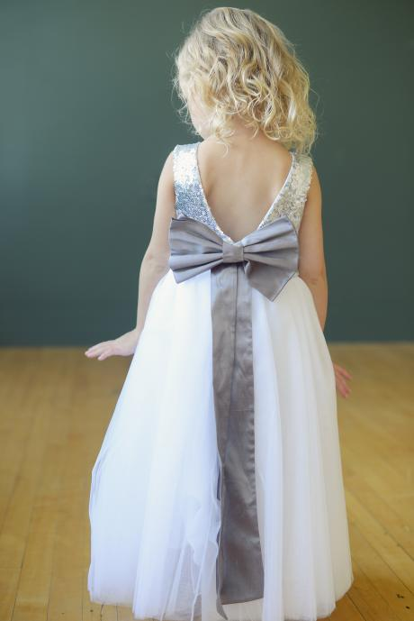 The back of a sequin flower girl dress in silver with a ivory tulle skirt. Th dress has a big bow in purple and a V back.