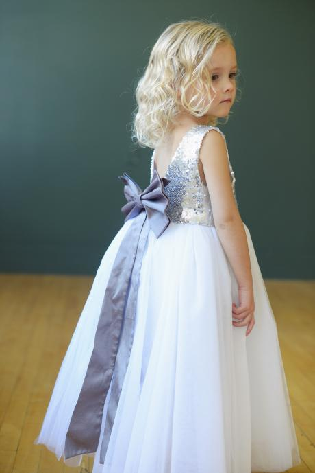 The back of a silver and white sequin flower girl dress with a v neckline. The dress has a big bow in a light purple and a full tulle skirt.