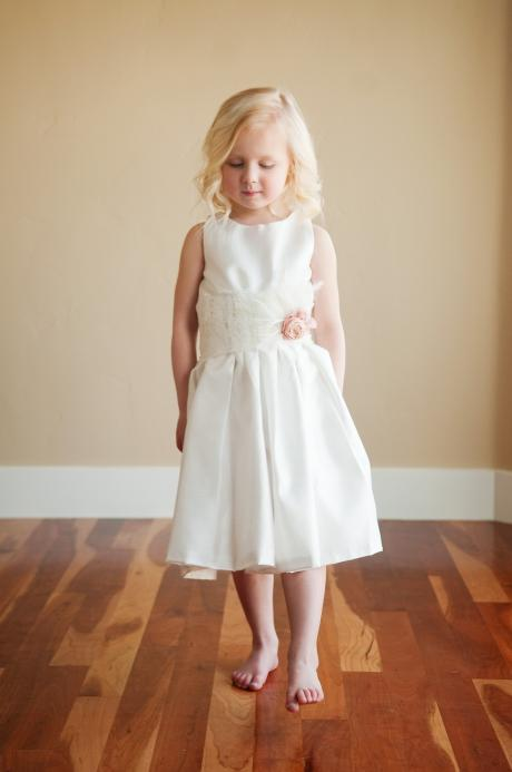 A young flower girl wearing a cotton flower girl dress at a wedding. The dress has a wide lace sash and the flower is available in all silk colours.