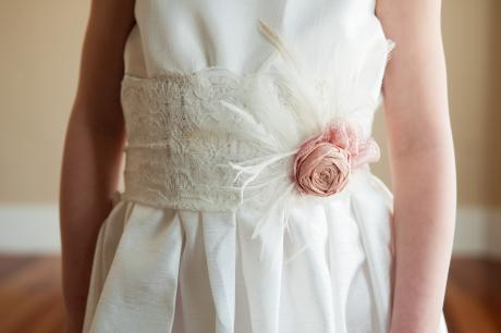 A close up of a young flower girl wearing an ivory and white lace flower girl dress with a lace sash with pink silk flower detail.