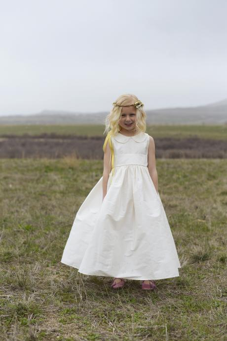 A flower girl standing in a field at a wedding wearing an ivory silk flower girl dress or junior bridesmaid dress with a Peter Pan collar and full silk sash.