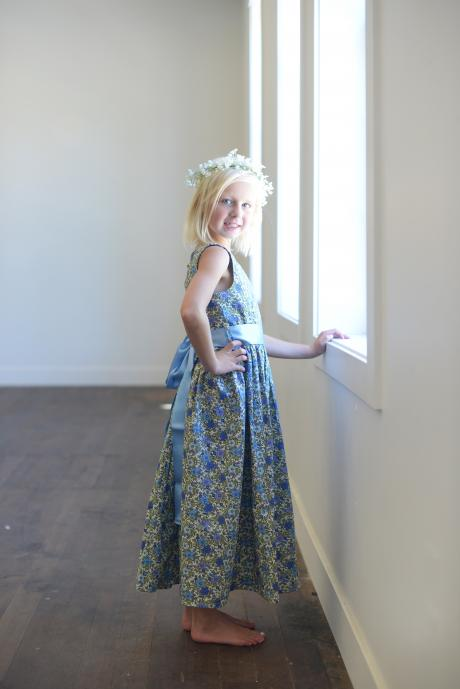 A young flower girl twirling whilst wearing a calf length blue floral flower girl dress with an ivory sash.