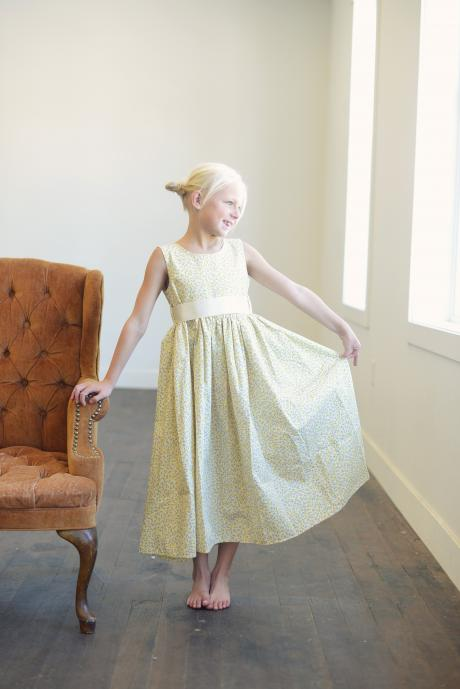 A girl wearing a lemon yellow floral bridesmaid dress standing next to a chair