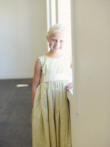 A girl standing next to a window wearing an ankle length floral flower girl dress