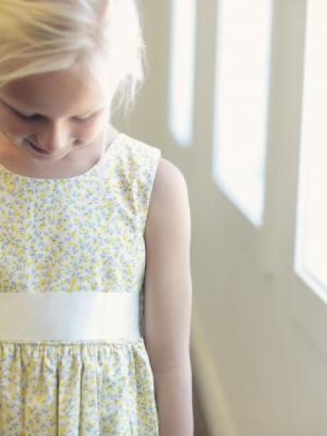 A close up of a girl wearing a yellow floral flower girl dress