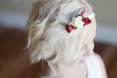 A little flower girl at a wedding wearing an ivory flower girl dress with a pretty pink and ivory flower headband,