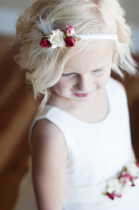 A young flower girl wearing an ivory flower girl dress with pretty ivory and pink flowers on the sahs and a tulle skirt. The flower girl is also wearing an ivory satin headband with pink and ivory flowers.