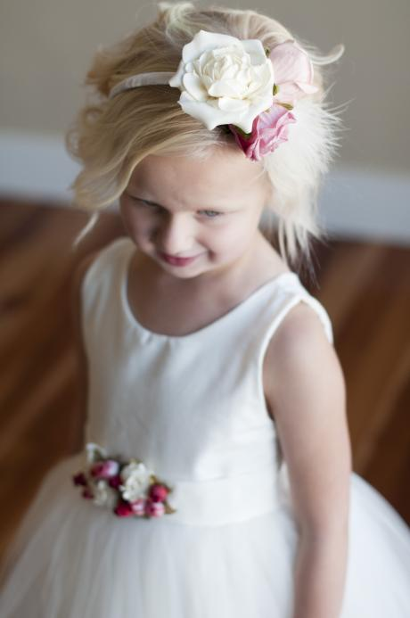 A flower girl wearing a very pretty ivory headband with big pink and ivory  flowers and smaller red ones.