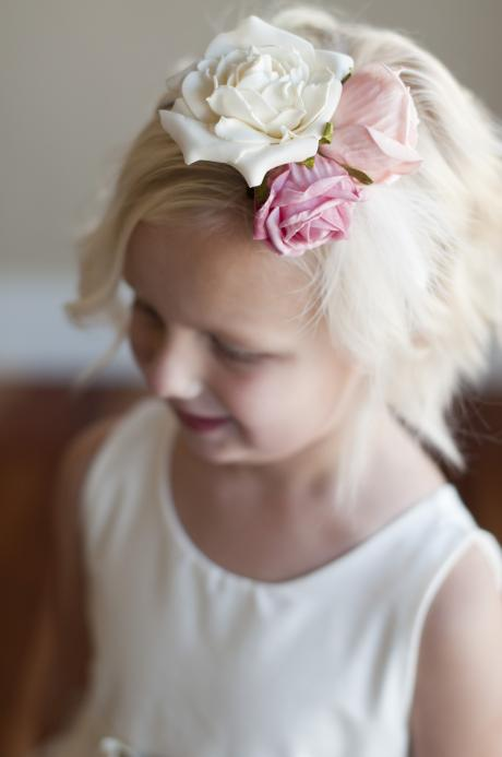 A flower girl wearing a very pretty ivory headband with big pink flowers and smaller ivory ones.