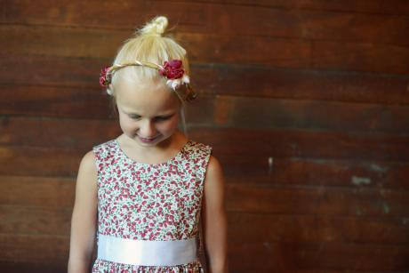 A photo of a girl in a floral flower girl dress with a red head crown and ivory sash