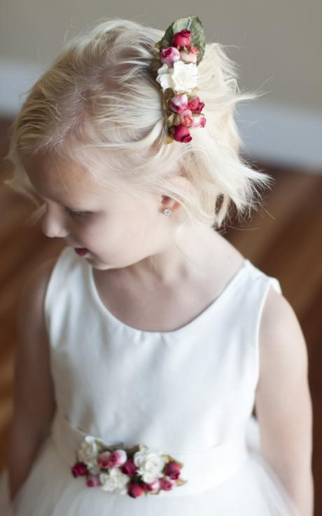 A flower girl wearing an ivory flower girl dress with red and pink roses on the belt and a rose bud hair clip