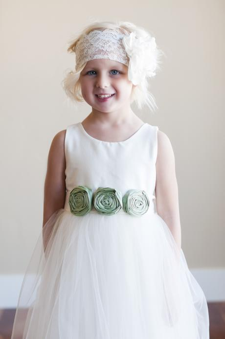A young bridesmaid at a wedding wearing a lace headband with large flower and an ivory flower girl dress with sage green flowers