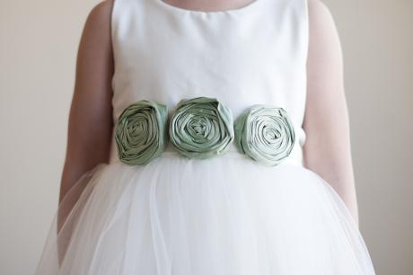 A close up of an ivory flower girl dress with roses in green on the sash.